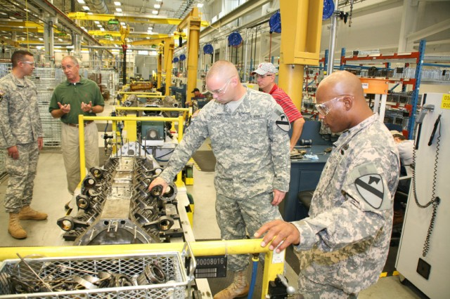 Soldiers examine engine parts on a disassembly line inside the depot's new 142,500-square-foot Powertrain Flexible Maintenance Facility as part of Anniston Army Depot's Operation Tell Your Story.