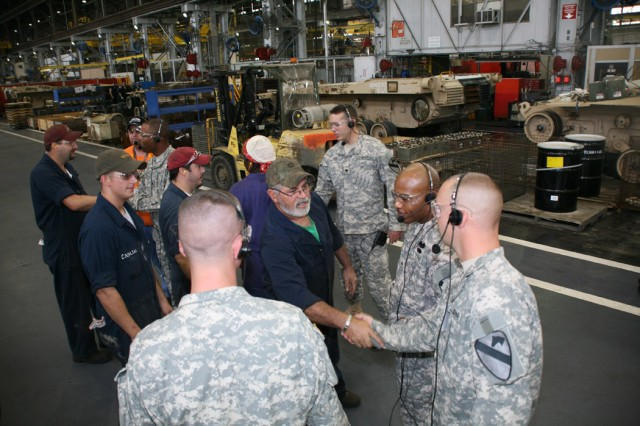 At Anniston Army Depot, mechanics in the Nichols Industrial Complex greet the Soldiers from 4th Brigade Combat Team on Sept. 16 during a visit that's part of Operation Tell Your Story.