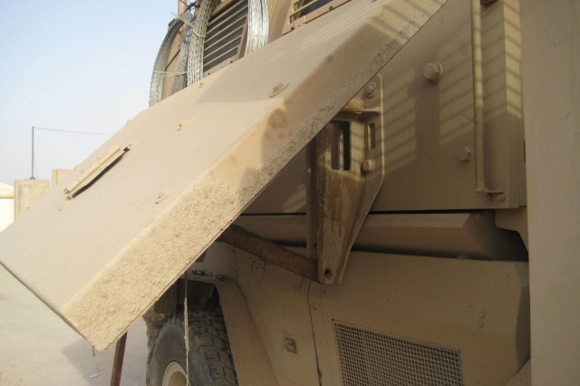 A pair of small brackets, designed by Sgt. Frank Lopez of Forward Support Company, 84th Engineer Battalion (Construction Effects), 130th Engineer Brigade, aids in the maintenance and repair of the new Mine Resistant Ambush Protected vehicle.