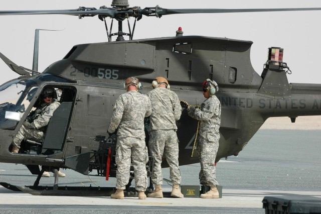 (From left to right) Staff Sgt. Brock Niehaus, Pfc. Joshua Cox  and Sgt. Danny Gordon, all armament avionics and electrical repair specialists, 2nd Squadron, 6th U.S. Cavalry Regiment, 25th Combat Aviation Brigade, rearm an OH-58 D Kiowa Warrior as its pilot looks on (far left) at Camp Buehring, Kuwait, Sept. 18.