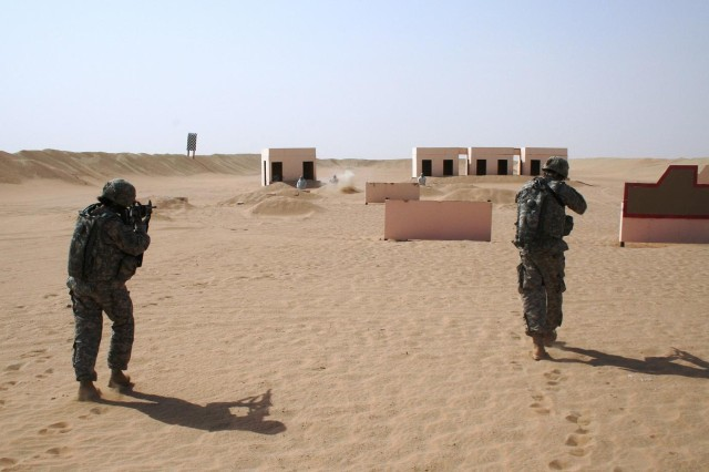 Sgt. Nancy Rodriguez (left), security analyst, Headquarters Headquarters Company, 25th Combat Aviation Brigade, and Spc. Jason Austin (right), heavy equipment operator, HHC, 25th CAB, approach an enemy compound in response to a simulated direct fire attack during live-fire rifle training outside of Camp Buehring, Kuwait, Sept. 18.