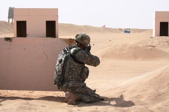 Spc. Jason Austin, heavy equipment operator, Headquarters Headquarters Company, 25th Combat Aviation Brigade, takes cover and returns fire toward an enemy vehicle in response to a simulated direct fire attack during live-fire rifle training outside of Camp Buehring, Kuwait, Sept. 18.