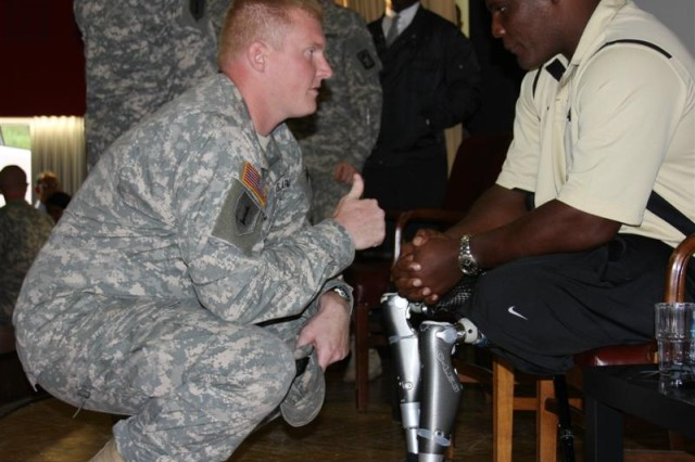 Lt. Col. Greg Gadson, a double amputee who wears the Power Knee 2, a next-generation powered prosthetic with artificial intelligence and sensor technology, shares his experiences during the rehabilitation process with a Soldier in Schweinfurt, Germany, Sept. 29. Gadson was the first to wear the advanced technology, and with it, he remains on active duty.