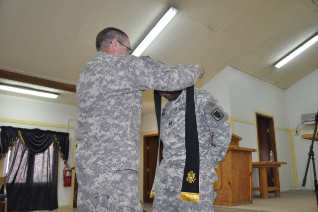 Chaplain (Lt. Col.) Thomas R. Shepard, the garrision chaplain for the Warrior Gospel Disciples, passes the responsibility of senior pastor to Chaplain (Capt.) David Mvondo by placing the stole around his shoulders.