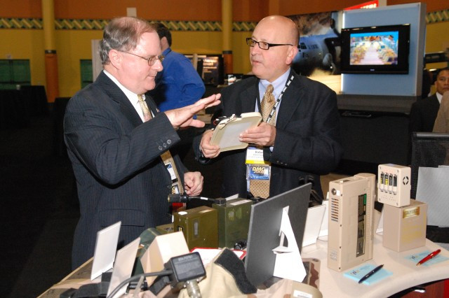 Rafael Casanova (right) of CERDEC Army Power's Battery Support team discusses the latest advancements in battery technology with Dr. Thomas H. Killion, deputy assistant secretary for Research and Technology/Chief Scientist, U.S. Army.