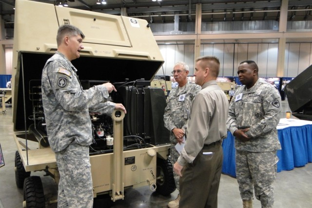 Tim White of PM AGSE shows Lt. Col. Russ Wygal, product manager for Aviation Ground Support Equipment, the engineering workings of the Reset Generic Aircraft Nitrogen Generator. In background are Staff Sgt. Dargan Hill and 1st Sgt. Terrence Powell.