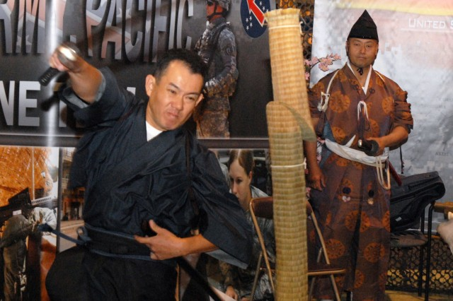 WASHINGTON D.C. -- Tadasu Takahashi, a representative of United States Army, Japan, slices through a rolled up mat while Mitsuo Onozaki looks on during the Japanese Warrior demonstration at the Association of the United States Army Oct. 5.  The Japanese Warrior demonstration was one of several cultural events hosted by United States Army, Pacific.
