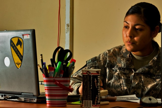 CAMP TAJI, Iraq-Pfc. Yamilette Bautista, from Woodland, Calif., a strength management clerk with the 1st Air Cavalry Brigade, 1st Cavalry Division, computes the personnel strength of 1st ACB battalions Oct. 1. Bautista is a Hispanic American who spent the first five years of her life living in Tequila, Mexico.