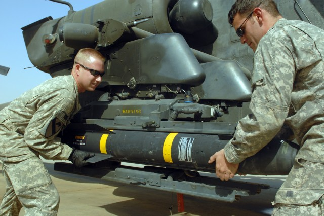 CAMP TAJI, Iraq - Spc. Sean McConnell (left), of Columbus, Ohio, and Spc. Scott Shaver, of Austin, Texas, load a Hellfire missile onto the mounting bracket on an AH-64D Apache helicopter, here, Oct. 1. Both Soldiers are armament electrical avionics repairers assigned to Company D, 1st Battalion, 227th Aviation Regiment, 1st Air Cavalry Brigade, 1st Cavalry Division.