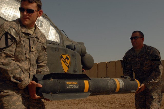 CAMP TAJI, Iraq - Spc. Scott Shaver, of Austin, Texas (left) and Spc. Bret Gibson, of Wichita, Kan., haul a Hellfire missile to load onto the mounting bracket of an AH-64D Apache helicopter, here, Oct. 1. Both Soldiers are armament electrical avionics repairers assigned to Company D, 1st Battalion, 227th Aviation Regiment, 1st Air Cavalry Brigade, 1st Cavalry Division.
