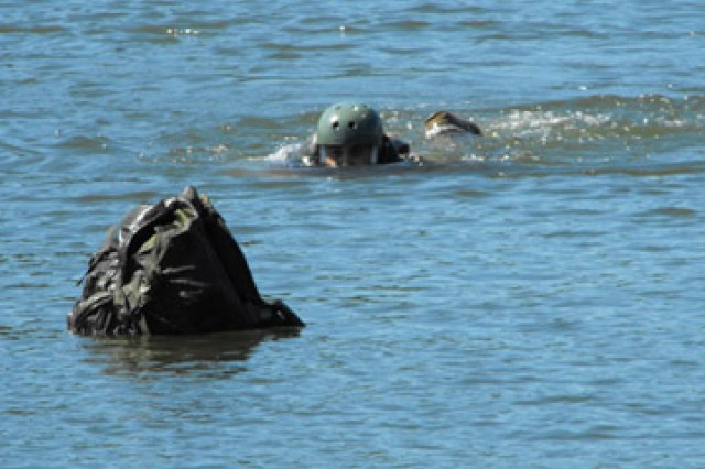 A test jumper swims for his pack before exiting Alligator Lake following a test helo cast with an LUH.