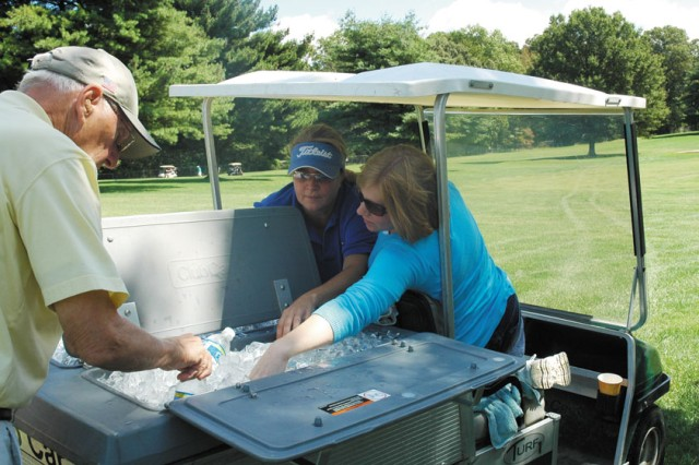 Tournament volunteers Robin Ingellis, left, and Christina Gray deliver ice and beverages to thirsty golfers. The tournament was named for Gray's husband, Joseph Gray, a U.S. Army Aberdeen Test Center contractor who was killed in a tank accident earlier this year.
