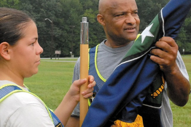 Command Sgt. Maj. Marvin Womack Sr. helps Sgt. Lisa Ortiz case the unit guidon after morning PT Aug. 28.