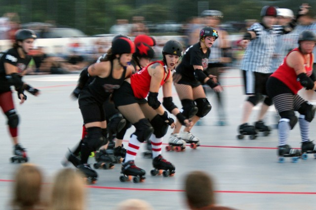 "Julia ""Souxsie Skoolyard"" Harrison (center, red jersey), Army spouse and member of the Savannah Derby Devils, performs a ""booty block"" to prevent an opponent's jammer from getting by her and scoring a point during a recent roller"