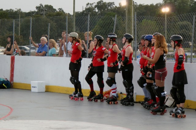 "Half of the red team of the Savannah Derby Devils waits for the call to action during a recent competition. From left (roller derby names listed): Lana Luck, Bellatris LeRage, Julia ""Souxsie Skoolyard"" Harrison, Annamistic, Rambling Rose, Disasstris, Ira Fuse (2), ReAnn Forcer, and Tsu Legit-2quit."