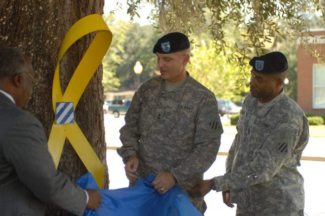 Major General Tony Cucolo, commanding general of the 3rd Infantry Division, Command Sgt. Maj. Jesse Andrews, command sergeant major of the 3rd ID, and Hinesville Mayor James Thomas unveil the yellow ribbon at a rededication ceremony to commemorate the 3rd Infantry Division's fourth deployment since Sept 11, 2001, at Victory Park in Hinesville, Oct. 1.