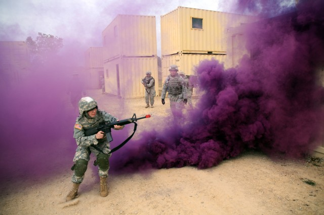 Smoke camouflages a Soldier's movements during a dismounted combat patrol at a Fort McCoy, Wis., training site.