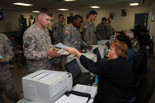 Administration specialist Kris Oakes (right) assists Staff Sgt. Robert McGuire of the 33rd Brigade Combat Team with the completion of his Department of Defense Form 214.
