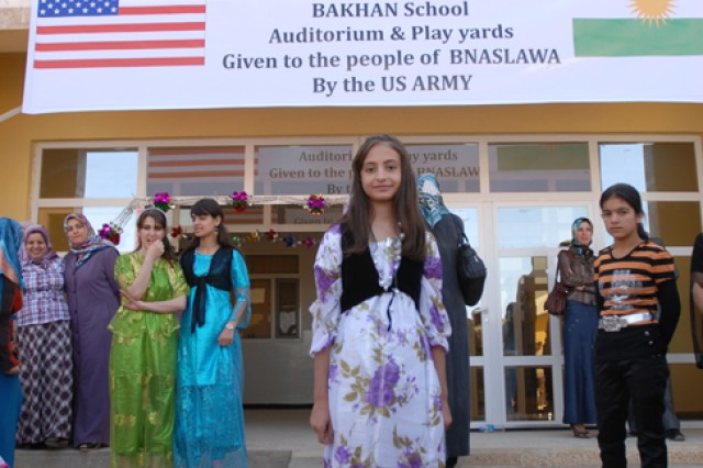 Zahra Azadin, 14, stands in front of her new school in the Bnaslawa district of Erbil, Iraq, Sept. 29. Zahra is one of 1,600 female students who began attending the school.