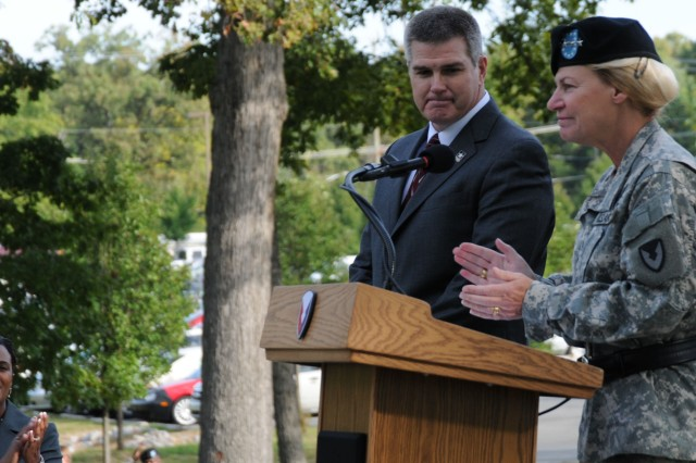 Gen. Anne E. Dunwoody, commander, Army Materiel Command, encourages applause for Jeff Parsons, executive director, Army Contracting Command, during a ceremony celebrating the command reaching full operations capability status.