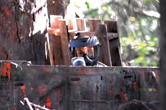 A red team Soldier peeks out from his hiding spot Sept. 29 during a round of paintball at the Woodlands Paintball Area.