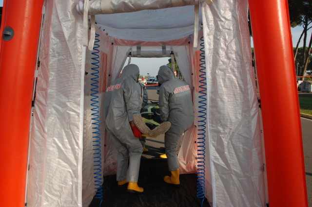 Italian Pisa firefighters begin the decontamination process of a contaminated role player during the joint Italian-American force protection exercise, Oct. 7.