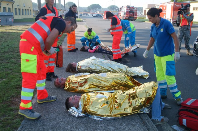 "(Left in orange) Members of the Italian Public Assistance and (right in blue) members of the Misericordia Assistance Service, a catholic association, treat simulated casualties and prepare them for transport to local Italian medical facilities during Exercise ""Tuscan Sun."" Oct.7."