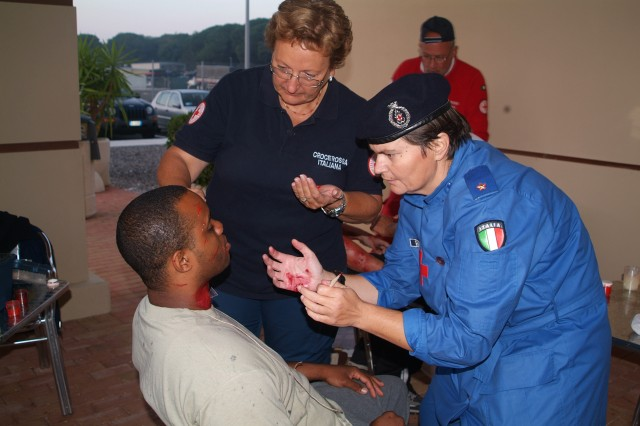 """Members of the Italian Red Cross put make-up on a role player prior to Exercise """"Tuscan Sun,"""" Oct. 7.  Red Cross """"make-up men"""" take specific training classes in order to make wounds look as realistic as possible."""
