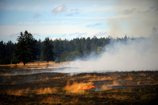 Fort Lewis prairie and grassland smolders after undergoing a controlled burn. The post worked with The Nature Conservancy to conduct prescribed burns on some of the 12,000 acres of prairie on Fort Lewis to rid them of invasive species like Scotch broom.
