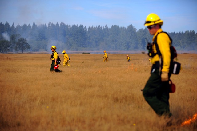 Firefighters use drip torches to light a fire on prairie and grassland on Fort Lewis.