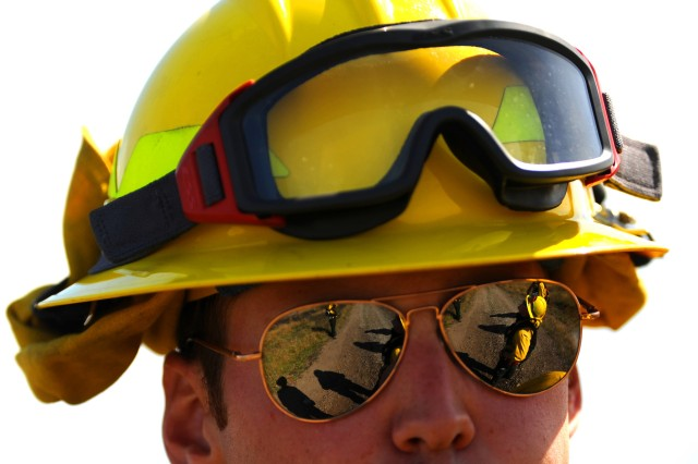 Fellow firefighters are reflected in John Richardson's sunglasses during a controlled burn on Fort Lewis.