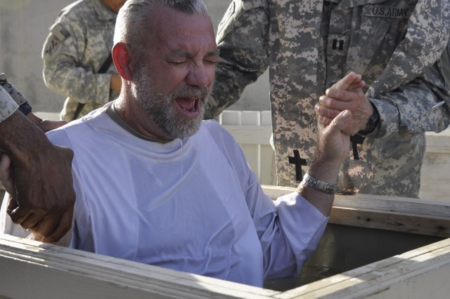 KANDAHAR AIRFIELD, Afghanistan -- Capt. Dmitri V. Kostyunin, a 143d Expeditionary Sustainment Command chaplain and an Army reservist from Leesburg, Fla., conducts a baptism on Oct. 4 outside the Fraise Chapel.