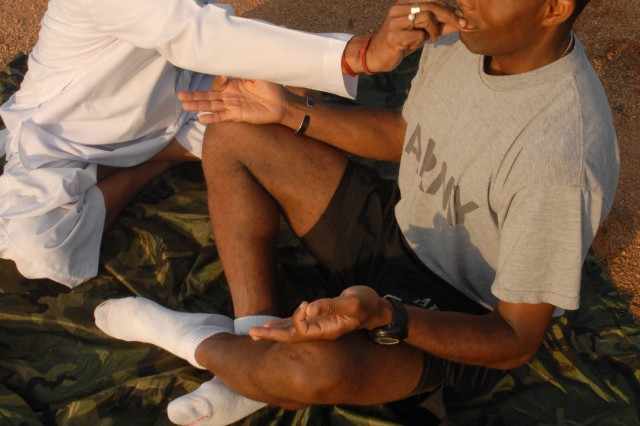 "CAMP BUNDELA, India- (Oct. 11, 2009) - Ram Dhani Bajpai, yoga instructor, holds 1st Sgt. Devin Winnegan's mouth shut to teach him proper breathing techniques during a yoga session at Camp Bundela in Babina, India, Oct. 11. Winnegan is the senior enlisted Soldier assigned to Troop B, 2nd Squadron, 14th Cavalry Regiment, ""Strykehorse,"" 2nd Stryker Brigade Combat Team, 25th Infantry Division. The instruction is part of a cultural exchange between the Indian Army and the U.S. Army. The Soldiers are in India in support of Exercise Yudh Abhyas 09. YA09, which is scheduled for Oct. 12-27, is a bilateral exercise involving the Armies of India and the United States. The primary goal of the exercise is to develop and expand upon the relationship between the Indian and U.S."