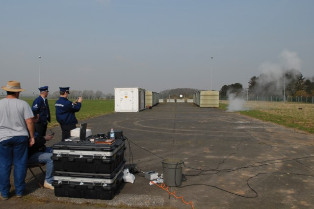 Brandon Howard (seated) and Luis Velez (left), from the Benelux Training Support Center, demonstrate of a mock improvised explosive device to a Belgian Federal Police team at the Alliance Home Station Training Area on ChiAfA..vres Air Base.
