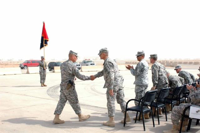 Col. Michael Lundy (left), commander, Task Force Wings, shakes the hand of Maj. Gen. Robert L. Caslen Jr. (center), commanding general, Multi-National Division-North and TF Lightning, as Command Sgt. Maj. Frank Leota, MND-N command sergeant major, applauds during a Transfer of Authority ceremony at Contingency Operating Base Speicher, Iraq, Oct. 10. (U.S. Army photo by Sgt. 1st Class Tyrone C. Marshall Jr., 25th Combat Aviation Brigade Public Affairs)