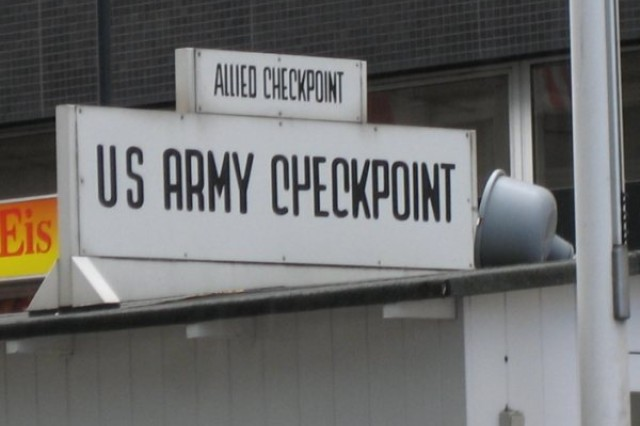 """The Wall is gone now, and along with it the armed guards, the minefield, and the """"shadows"""" assigned by the Warsaw Pact intelligence services, but the small checkpoint and original sign still mark the last stop before entering East Berlin."""