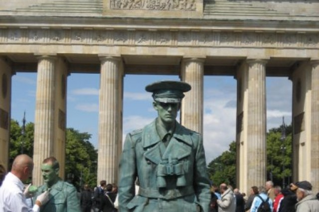 """The Brandenburg Gate, now as sparkling clean as when it was built, has enterprising performance artists who work the crowd for photo opportunities.  The tarnished """"statue"""" in the foreground is actually a man in makeup and costume.  Another artist preps for his turn in the background."""