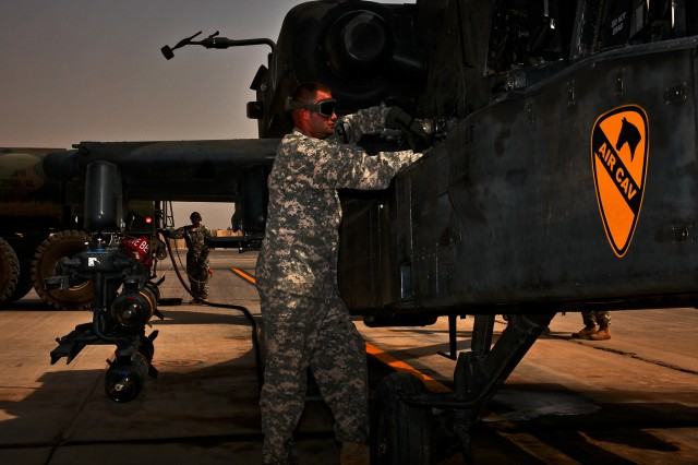CAMP TAJI, Iraq-After hooking a fuel line up to an AH-64D Apache attack helicopter, Spc. Greg Lofton, from Houston, a petroleum supply specialist monitors the fuel quantity panel while refueling, here, Oct. 9.