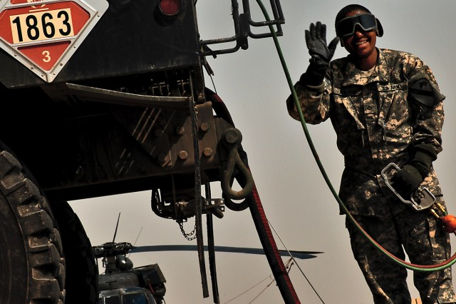 CAMP TAJI, Iraq-Spc. Kanedria Wilson, from Louisville, Ky., a petroleum supply specialist, signals that fuel has started to flow from the refuel truck to the AH-64D Apache attack helicopter, here, Oct. 9.
