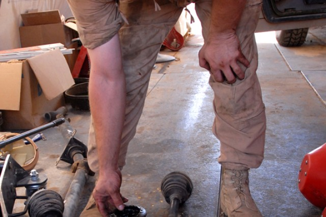 BAGHDAD - Spc. Charles Marshall, a light-wheeled vehicle mechanic, from Wheeling, W.V., indicates a half-shaft that is separated from its base.  Bolts attached to the base become loose for various reasons:  general wear and tear, constant vibration from uneven roads, re-installments for upgrade purposes or work done to the brakes.