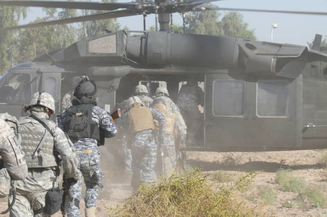"""BAGHDAD-U.S. cavalry scouts from """"1st Squadron, 7th Cavalry Regiment, 1st Brigade Combat Team, 1st Cavalry Division, and Iraqi policemen from the 1st Battalion, 2nd Brigade, 1st Federal Police Division, run to board a UH-60 Blackhawk helicopter after sweeping a stretch of the Baghdad-Diyala highway for improvised explosive devices.  The combined force conducted three air insertions, all in clear view of the busy highway.  One purpose of the mission was to deter insurgents by showing them how quickly and unexpectedly the combined force can arrive."""