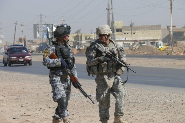 BAGHDAD-Milpitas, Calif. native Spc. Glenn Escano (right), 1st Squadron, 7th U.S. Cavalry Regiment, 1st Brigade Combat Team, 1st Cavalry Division, chats with an Iraqi policeman from the 1st Battalion, 2nd Brigade, 1st Federal Police Division, while sweeping a highway for improvised explosive devices.  The combined air assault force swept three separate urban stretched of the Baghdad-Diyala highway in just a few hours.