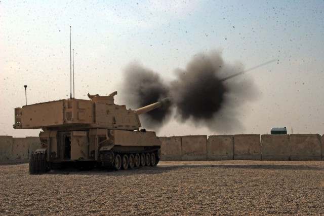 CAMP TAJI, Iraq- Smoke and dust rise as an M109A6 155mm howitzer assigned to 1st Battalion, 82nd Field Artillery, 1st Brigade Combat Team, 1st Cavalry Division, fires during a visit from Brig. Gen. John Murray, the deputy commanding general for maneuver, 1st Cavalry Division, and Gen. Ayad, the Rusafa area command chief of staff, to Firebase Mayhem, here, Oct. 8.