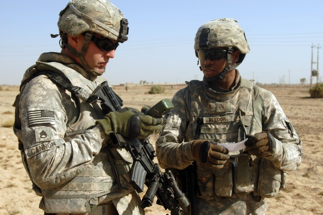 TAJI, Iraq - Staff Sgt. William Cannon (left), of Taylor, Mich., and Sgt. Jhonny Beldor, of Fredericksburg, Pa., confer about directions during a patrol near Taji Oct. 5. Both non-commissioned officers are artillerymen assigned to Company A, 1st Battalion, 82nd Field Artillery Regiment, 1st Brigade Combat Team, 1st Cavalry Division.