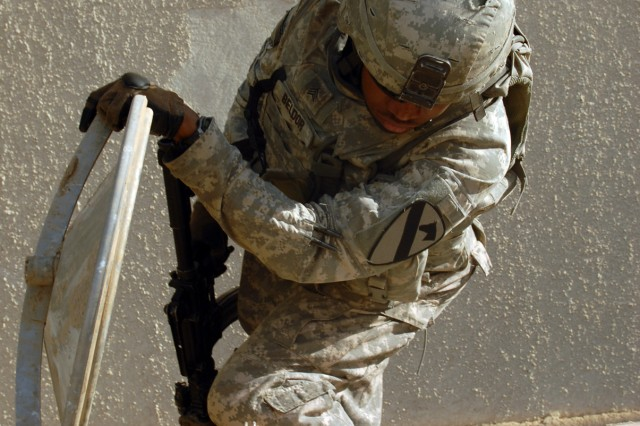 """TAJI, Iraq -Sgt. Jhonny Beldor, an artilleryman from Fredericksburg, Pa., searches for weapons during a joint patrol with the Iraqi Army in the Taji area, Oct. 5. """"I like the excitement when we get to do stuff like this instead of just sitting on the [forward operating base],"""" said Beldor. """"This is our first time in this area and we want to get to know the people here."""" Beldor is assigned to Company A, 1st Battalion, 82nd Field Artillery Regiment, 1st Brigade Combat Team, 1st Cavalry Division."""