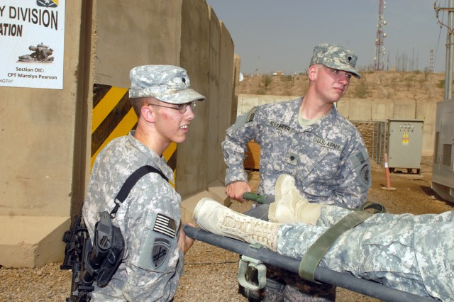 CAMP LIBERTY - Spc. Christopher Myers (left), of Lowell, Ark., and Spc. Christopher Alexander, of Alma, Ark., load a litter onto an ambulance outside the Division Special Troops Battalion aid station, here, Oct. 9. Both Soldiers, who are assigned to the 362nd Tactical Psychological Operations Company, DSTB, 1st Cavalry Division, took part in ambulance evacuation training.
