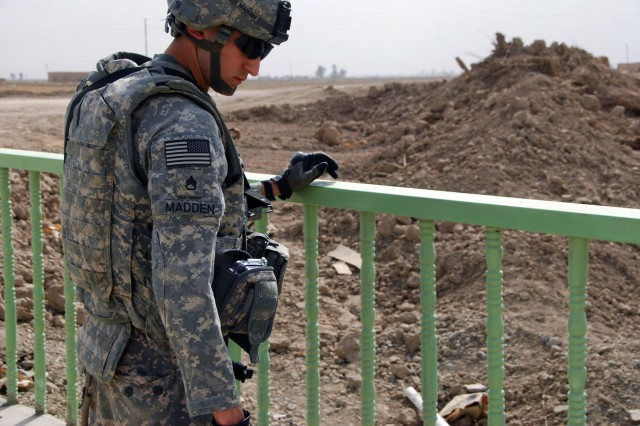 TAJI, Iraq- Cambridge, Mass. native, Staff Sgt. Carlos Madden, a civil affairs team leader attached to the 1st Battalion, 82nd Field Artillery Regiment, 1st Brigade Combat Team, 1st Cavalry Division, inspects the progress of a guardrail on the Odessa Bridge, Oct. 9.  The troops visited two bridge projects in the Taji area, north of Baghdad, that the battalion essential services team oversees.