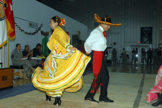 """CAMP LIBERTY, Iraq - Staff Sgt. Alma Selvera (left), of Oklahoma City, Okla., and Sgt. 1st Class Frank Rodriguez, of San Marcos, Texas, perform a traditional Jalisco Mexican dance as part of the group """"Raices Mexicanas"""" at the Multi-National Division-Baghdad Hispanic Heritage Month Observation, here, Oct. 9. The dance originates in the Mexican state of Jalisco. Rodriguez is the equal opportunity advisor for MND-B. """"I thought it was wonderful. I thought everybody had a good time,"""" said Rodriguez. """"First and foremost, it gave a little bit of education and second, it let the Soldiers have fun."""" Selvera is a dental assistant assigned to 502nd Dental Company, 1st Medical Brigade, Multi-National Corps-Iraq."""