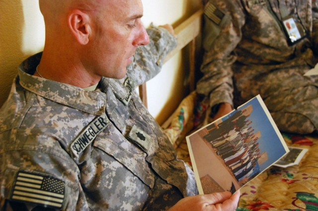 TAJI, Iraq- Ozark, Ala. native, Lt. Col. Eric Schwegler, commander of the 1st Battalion, 82nd Field Artillery Regiment, 1st Brigade Combat Team, 1st Cavalry Division, views a picture of Sheik Abdullah and his Sons of Iraq comrades during a visit, Oct. 9. Schwegler and his Soldiers visited Abdullah to discuss areas of concern for the people of his village.