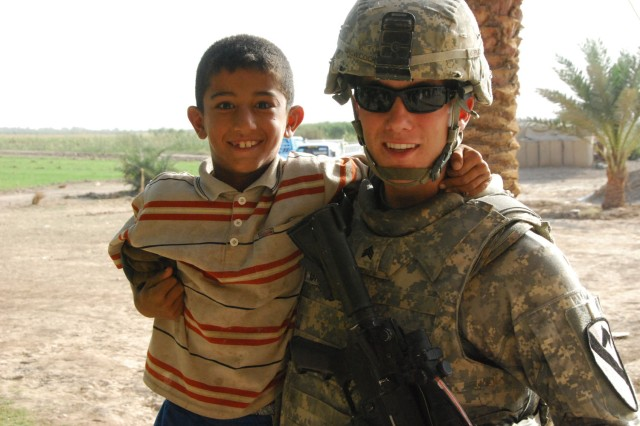 TAJI, Iraq- Winnemucca, Nev. native, Sgt. Buck Growcock, a squad leader assigned to the 1st Battalion, 82nd Field Artillery Regiment, 1st Brigade Combat Team, 1st Cavalry Division, poses for a picture with one of Sheik Abdullah's grandchildren, Oct. 9.  Growcock and other Americans visited Abdullah and his family to strengthen the friendship between U.S. troops and local Iraqi people.